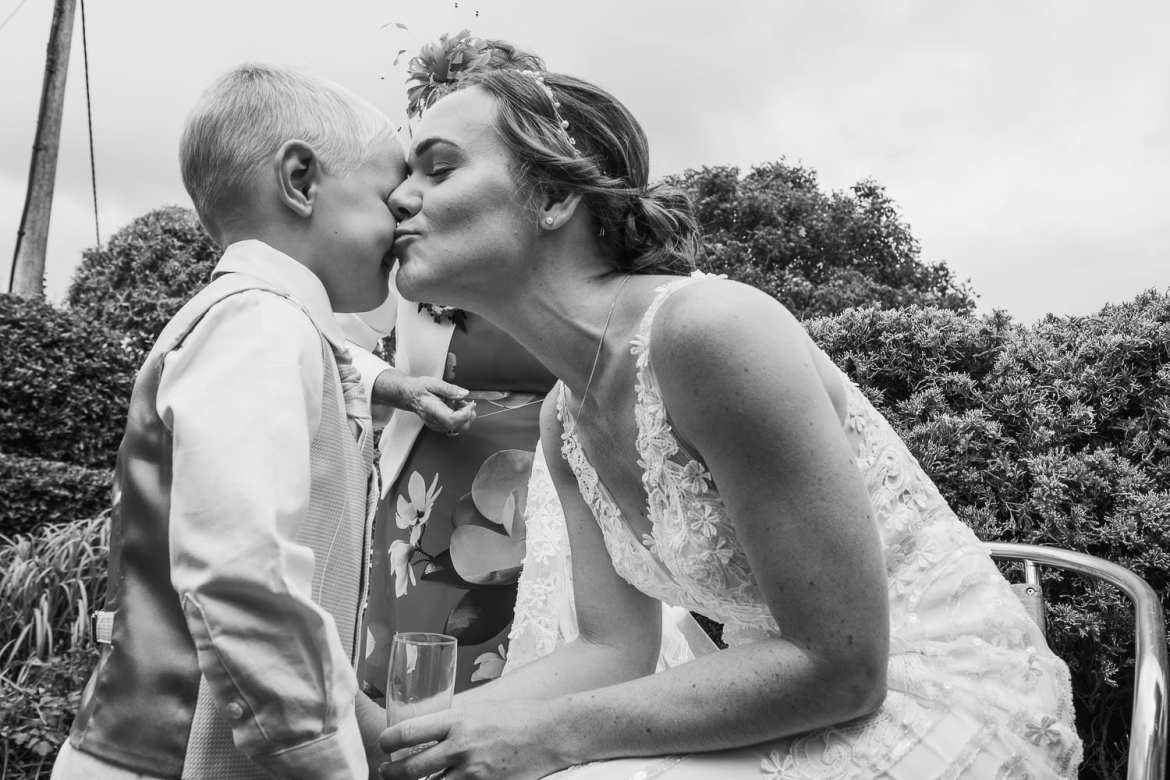 The bride kisses the page boy on his cheek