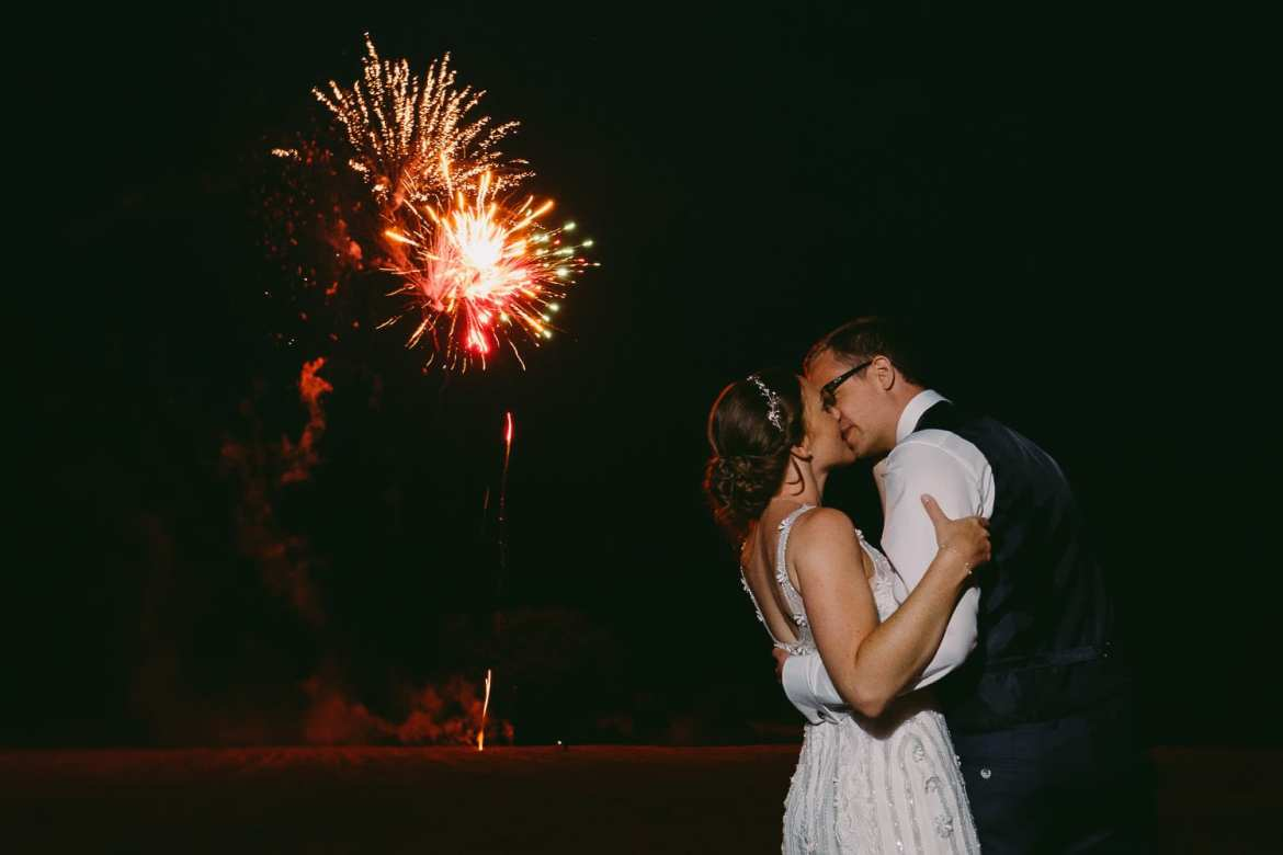 The bride and groom kiss while fireworks explode on the background