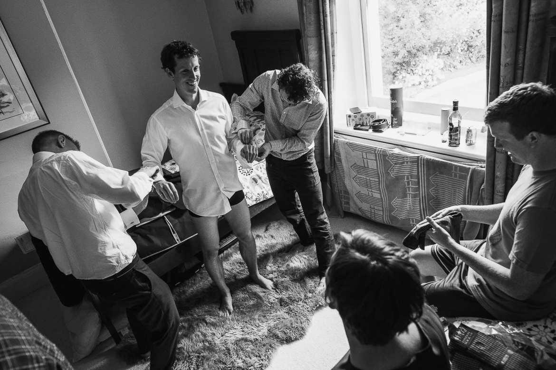 Groomsmen getting the groom reaqdy