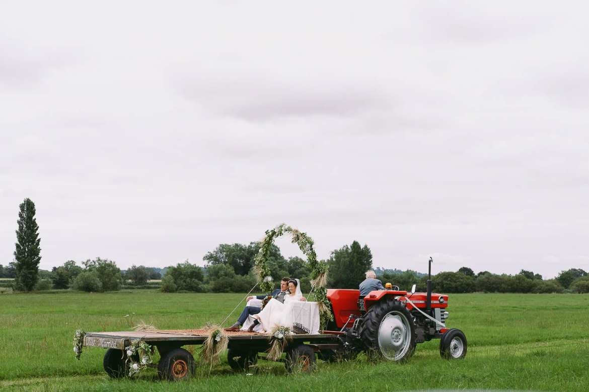 The bride and groom travel to the reception on a tractor