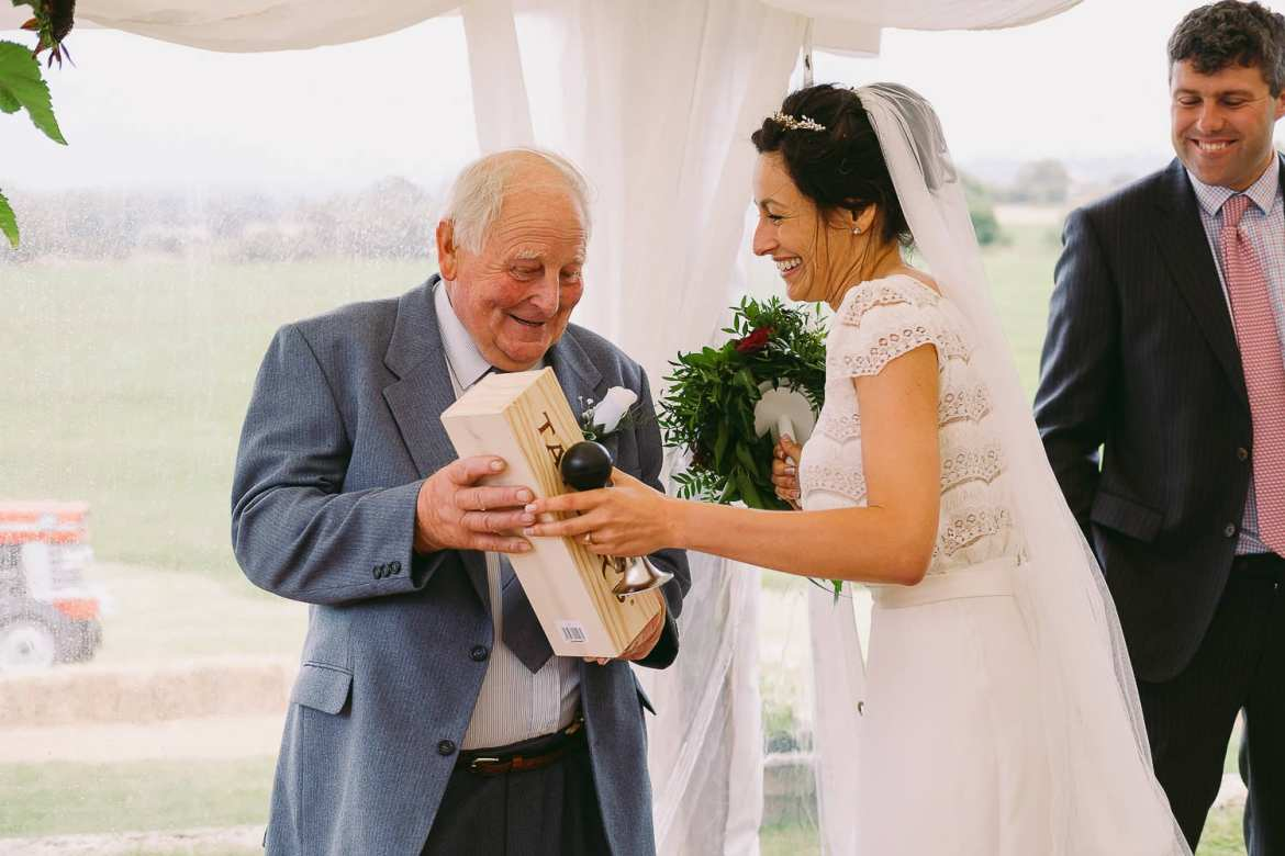 The bride gives her grandfather a bottle of whiskey