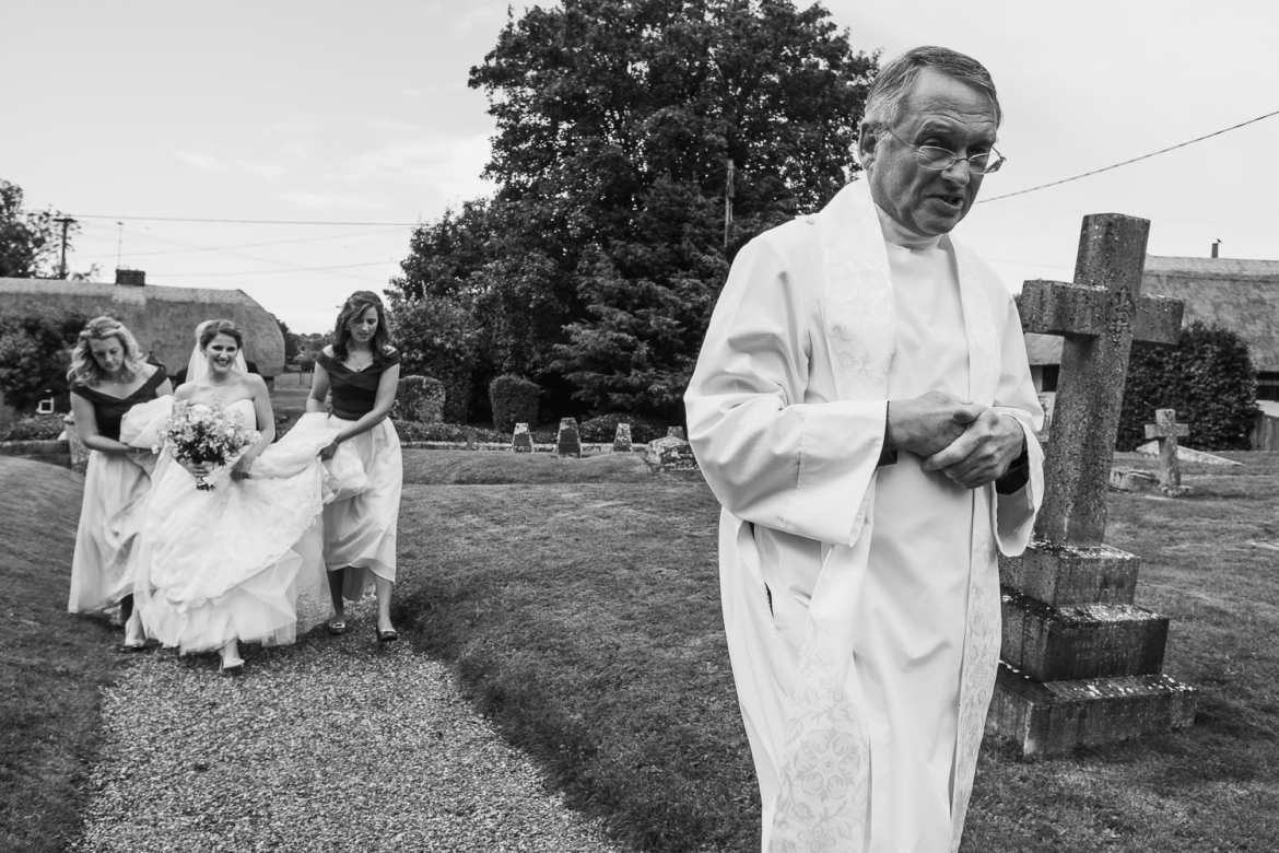 The vicar walks ahead of the bride and bridesmaids