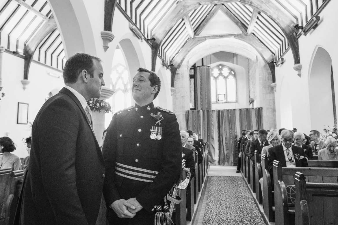 The groom jokes with his best man at St. Mary's Church in Codford