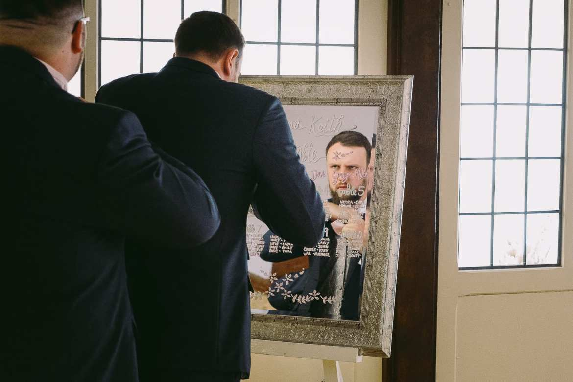 Groom does hi cravat in the mirror