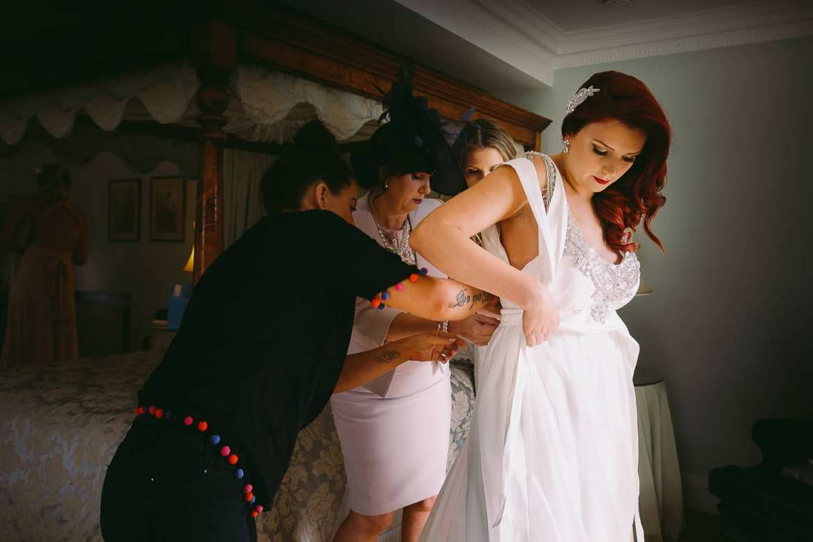 The bride is helped into her dress