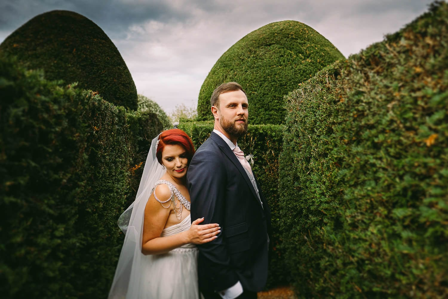The bride hugs the groom in the gardens at Birtsmorton court