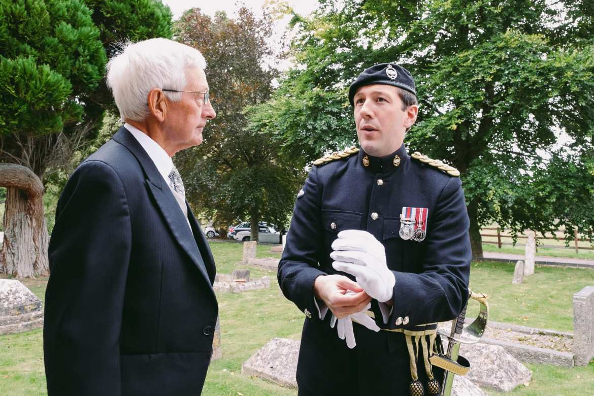 The groom in military uniform chats to a guest