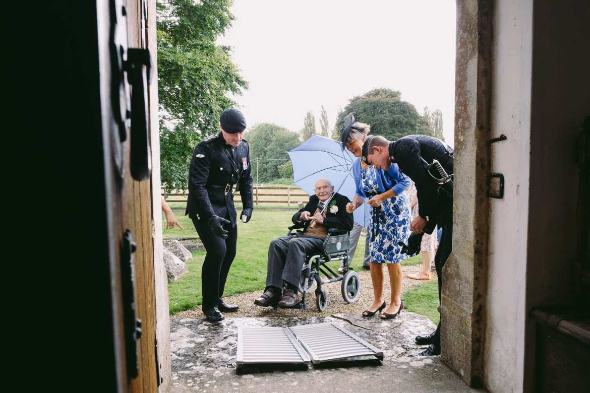 Granddad in a wheelchair is helped into the church
