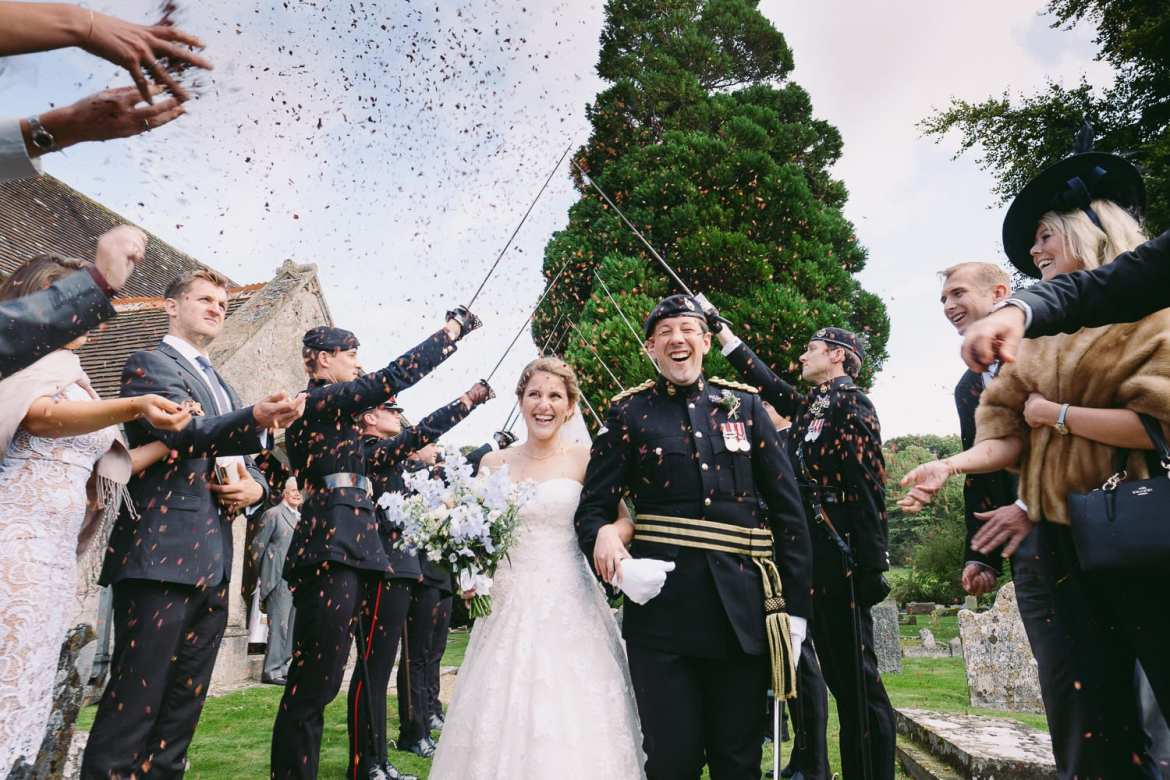 The guard of Honour raise their swords as wedding guests throw confetti