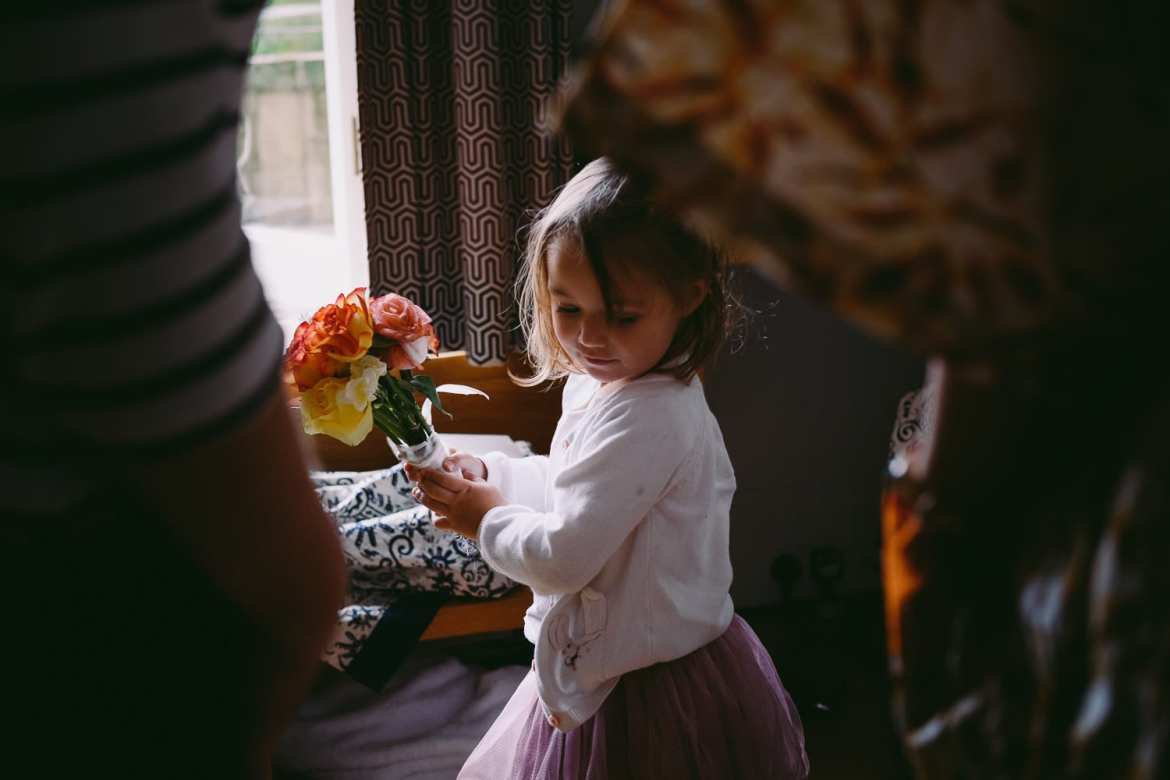 Flower girl with bouquet during bridal prep