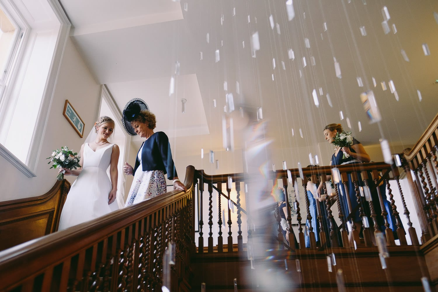 The mother of the bride walks down the stairs at coeley manor