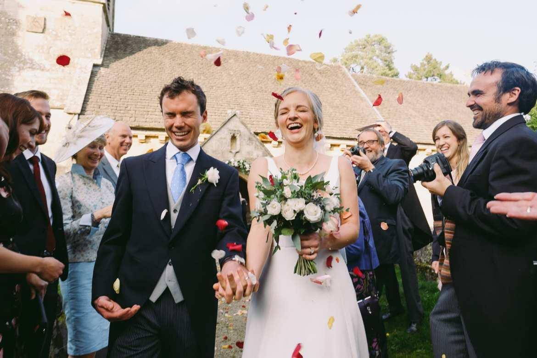 Bride and groom walk through the confetti