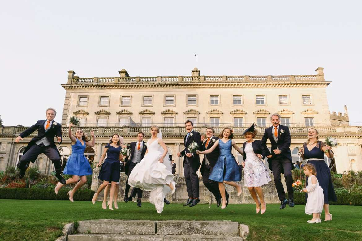 Bride and grooms family jumping shot outside Cowley Manor