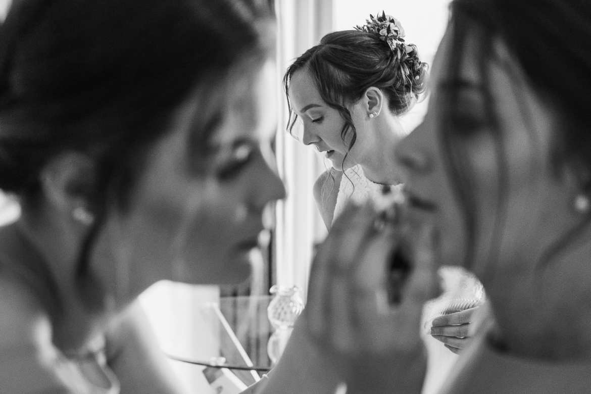 Bridesmaids do final touches to their makeup with the bride in the background