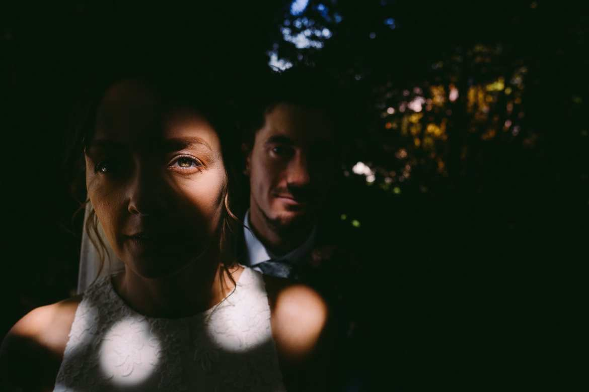 A portrait of the bride and groom under the trees