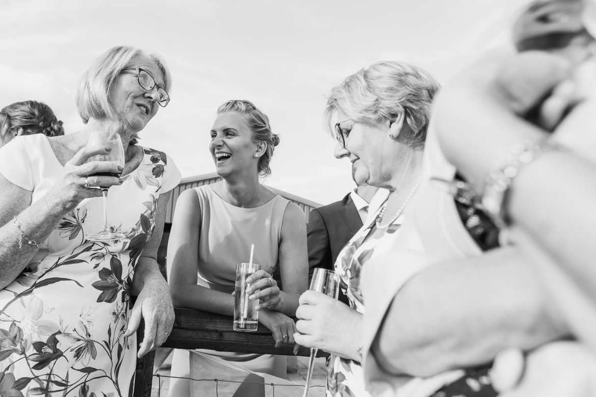 Wedding guests chat to a bridesmaid