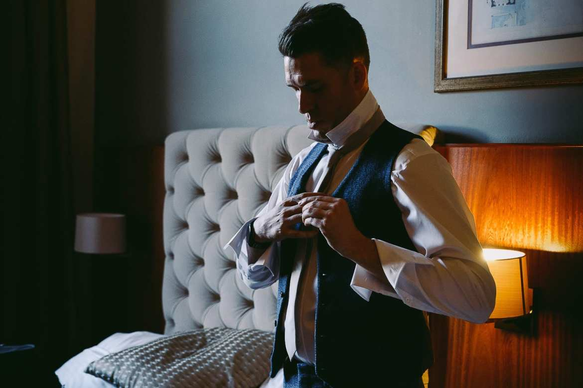 The groom puts his suit on