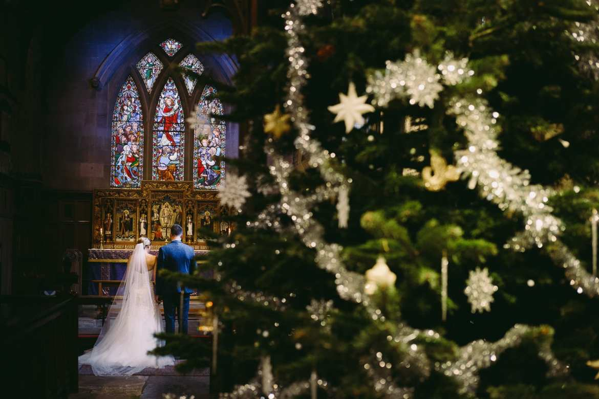 The bride and groom with a Christmas tree