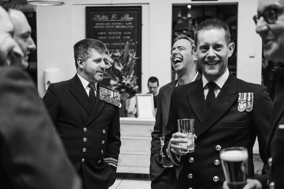 The groom and Military guests laughing