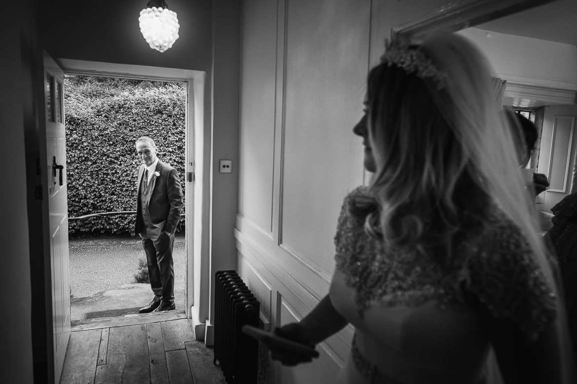 Dad waits outside the bridal suite as the bride comes out to see him