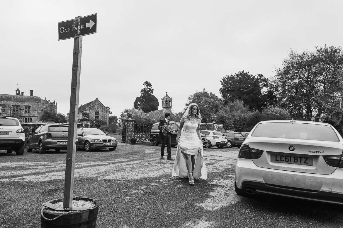 The bride holds her dress up as she walks across the car park for some portraits