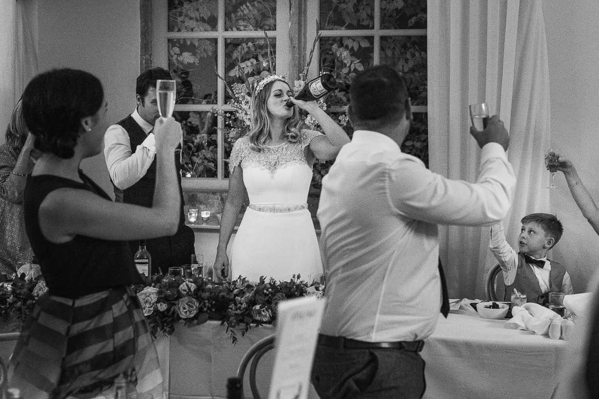 The bride drinks straight from the champagne bottle during the toast