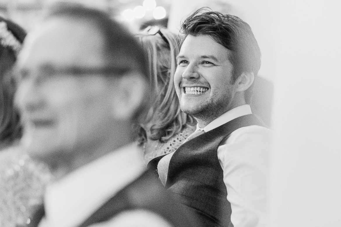 The groom smiles during The best man's speech