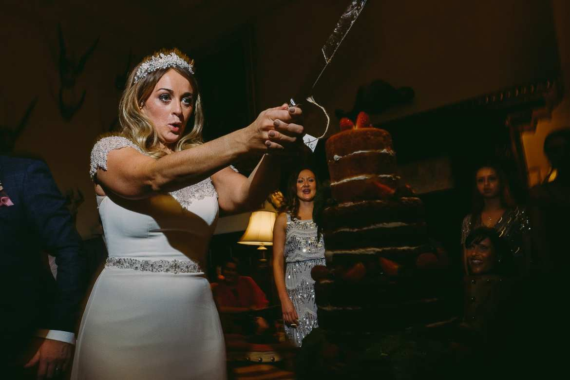The bride wields the knife above the cake