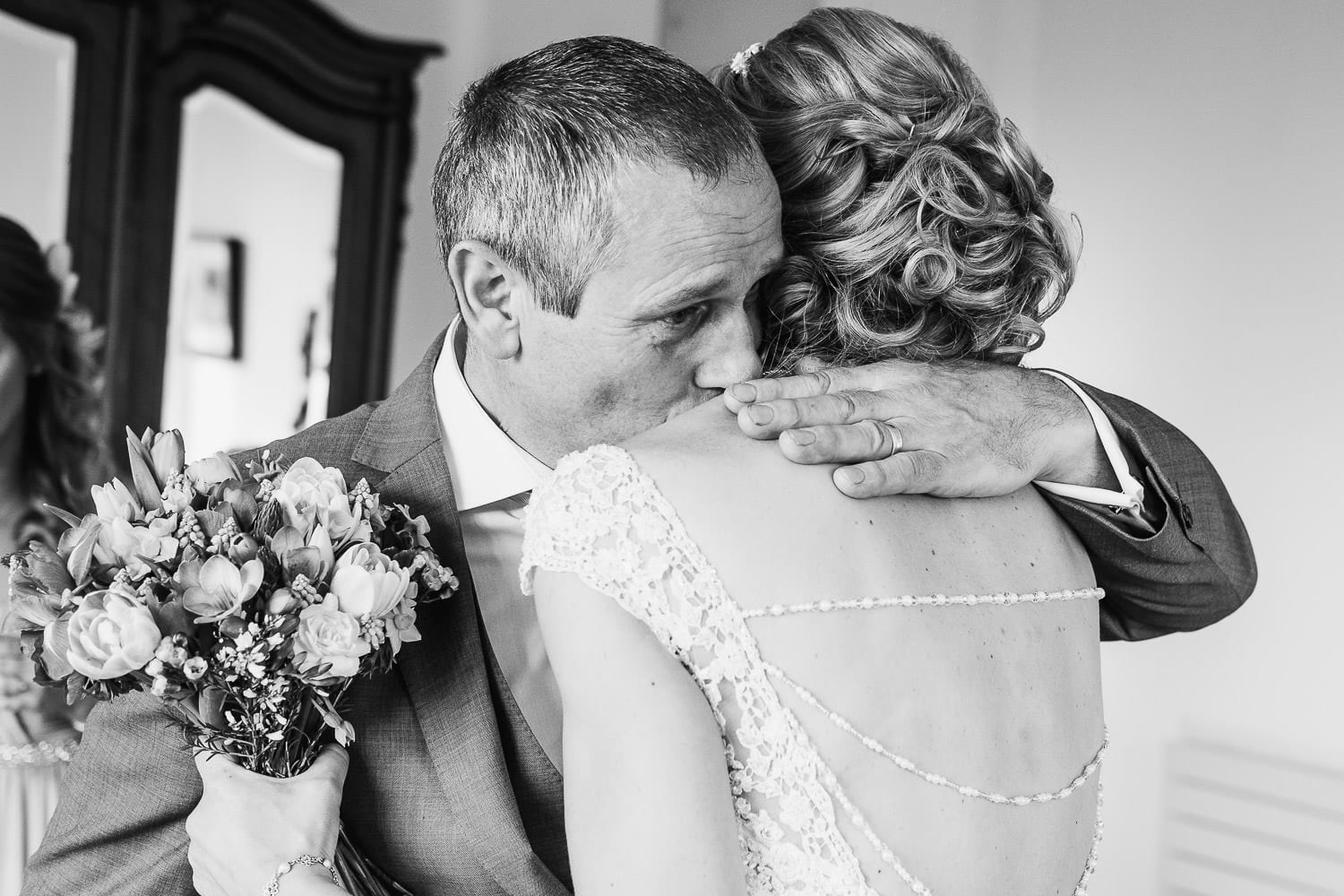 The father of the bride cries as he hugs his daughter