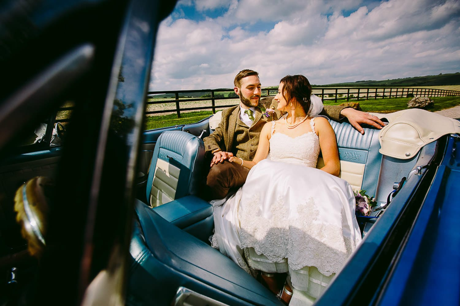A portrait of the bride and groom in the wedding car