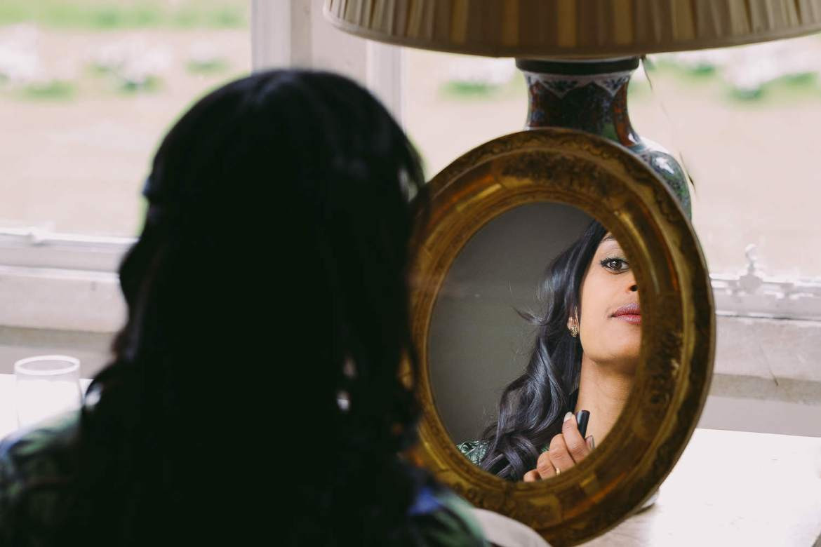 THe bride doing her makeup in the mirror
