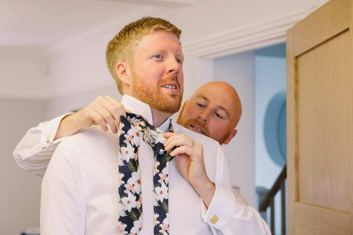the best man helps the groom with his tie