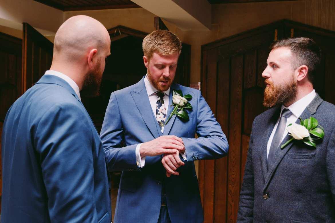 The groom checks his watch in the church
