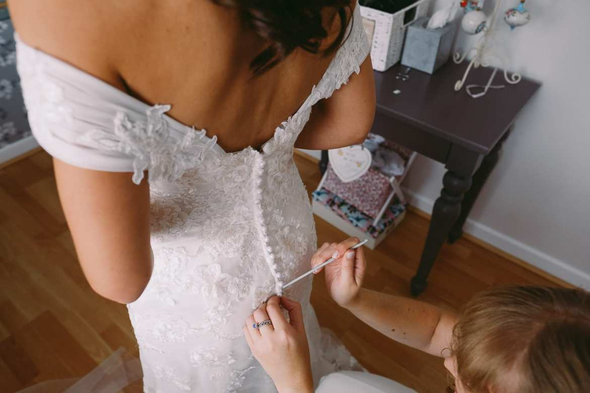 a bridesmaid helps the bride into her dress