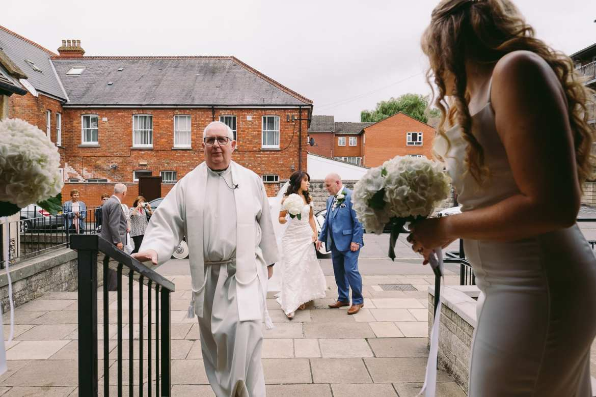 the bride and her father walking towards the church