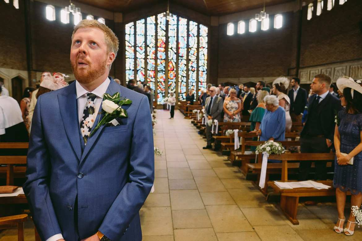 the groom looks nervous as he waits at the altar