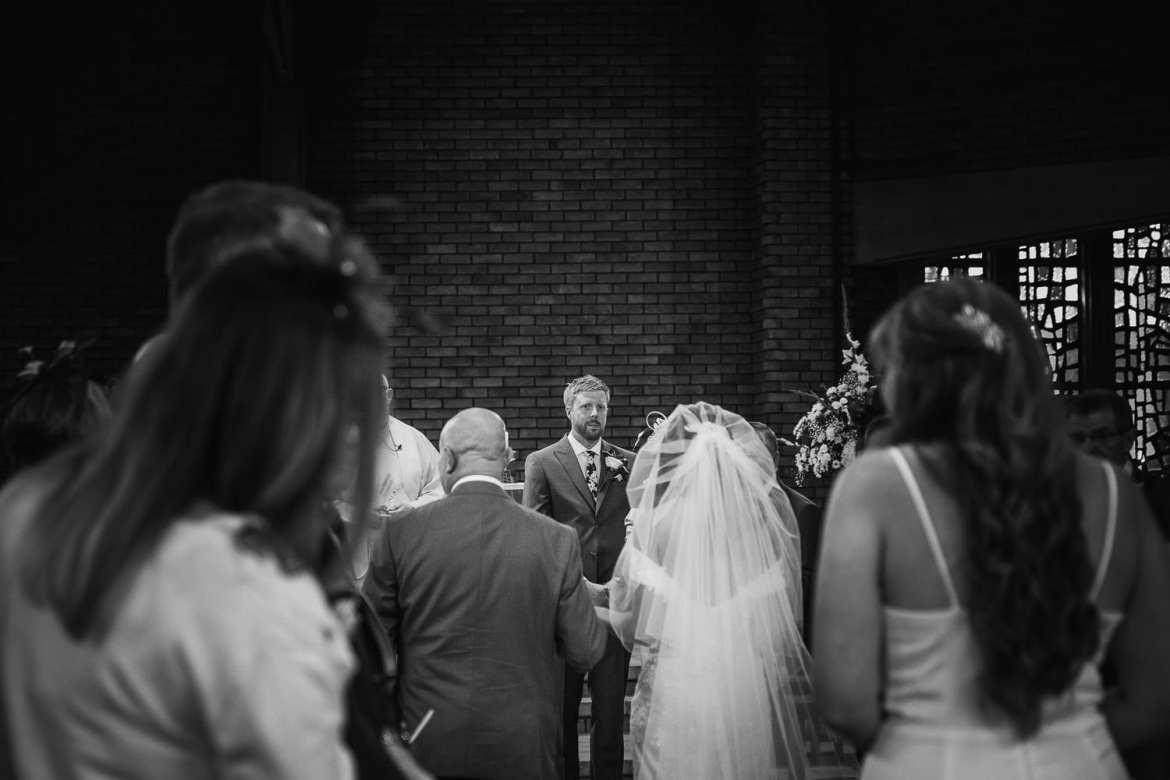a view of the groom as the bride walks up the aisle