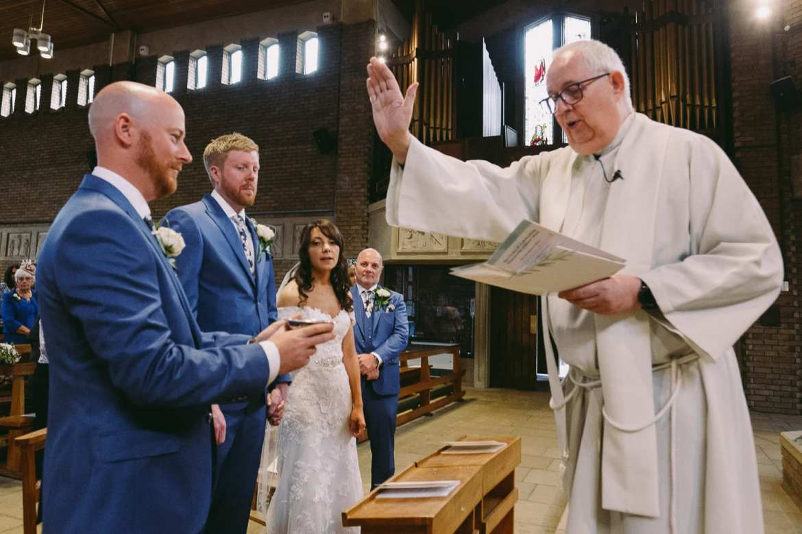 The vicar at Holy Rood Church holds his hand up and blesses the rings
