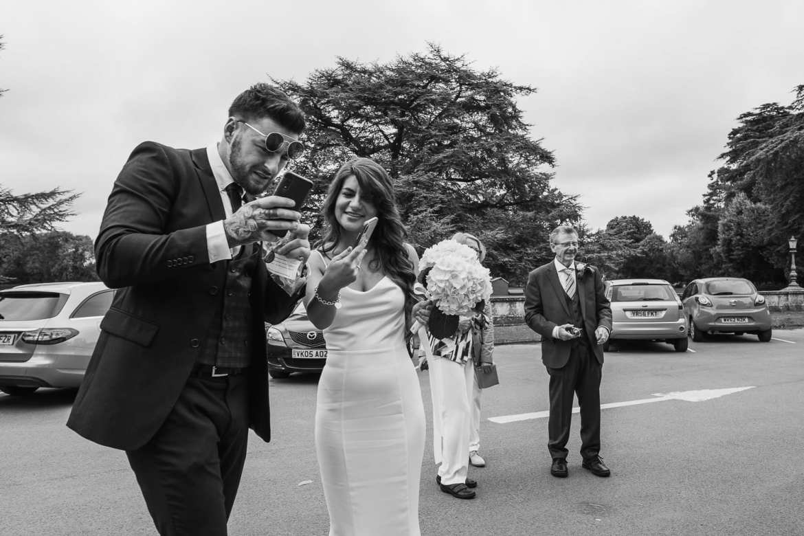 a bridesmaid and her boyfriend comparing images on their phones