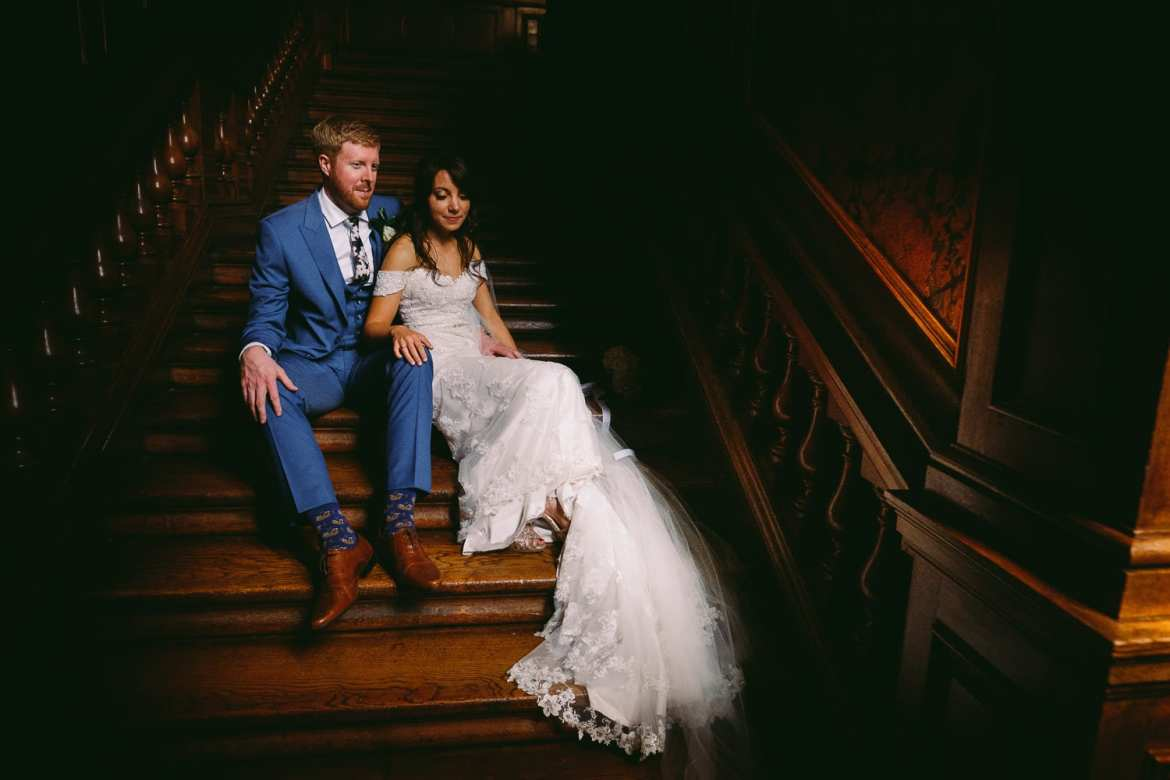 the bride and groom sitting on the stairs at westonbirt house