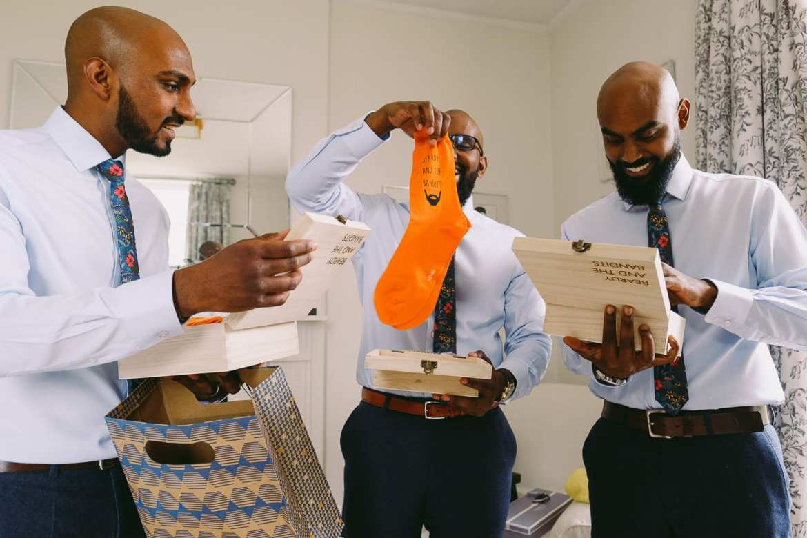 the groomsmen open their presents of socks