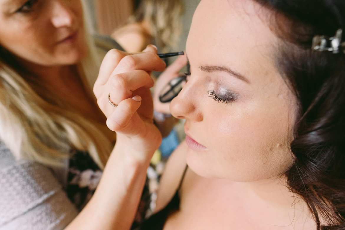 Bride having her make up done in the morning