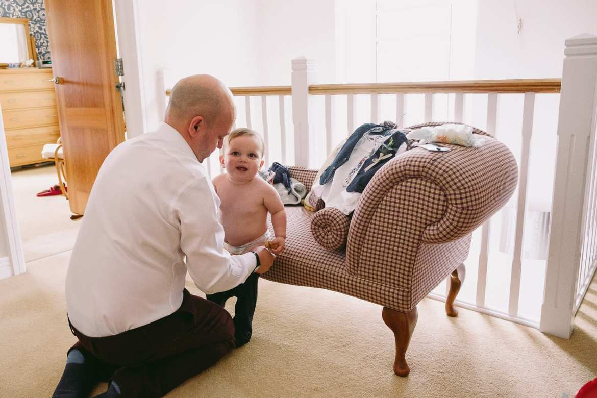 Groom getting their son ready for the wedding