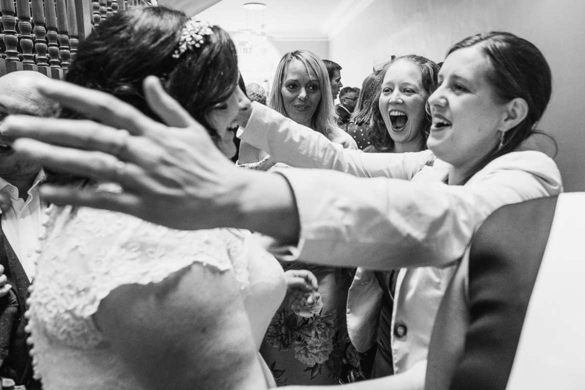 Bride getting a hug from her friends