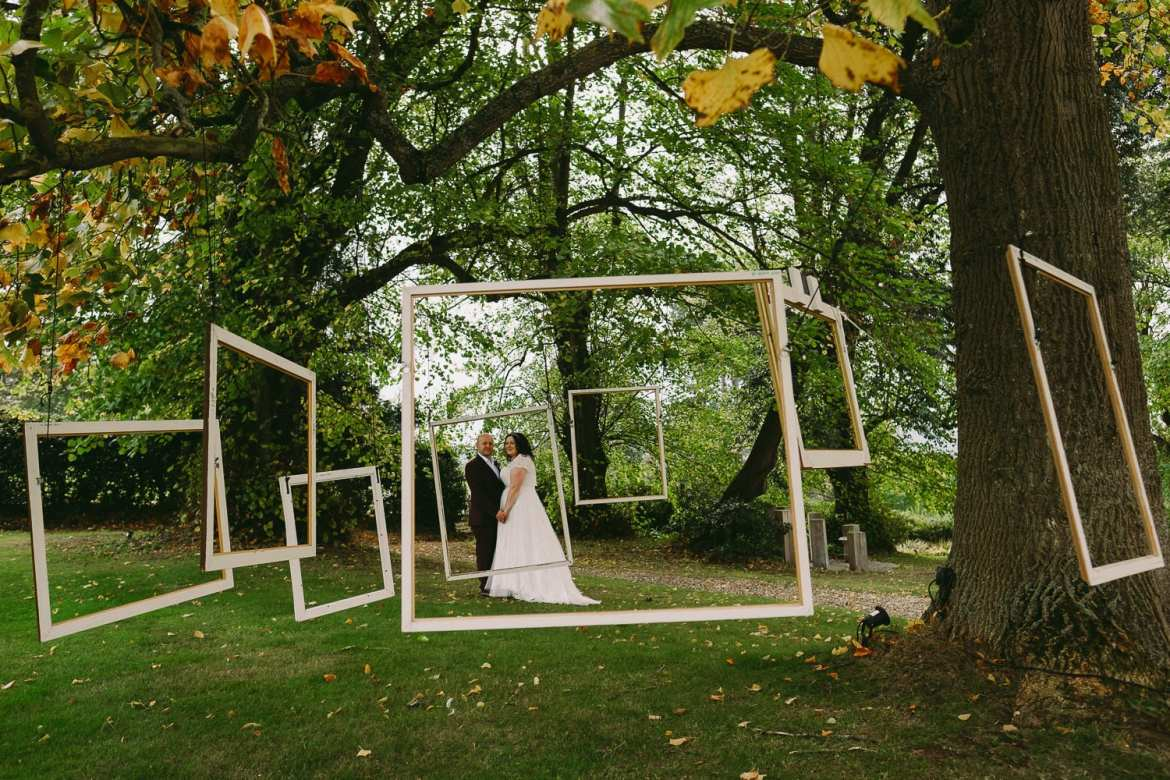 Bride and groom through tree hanging picture frames