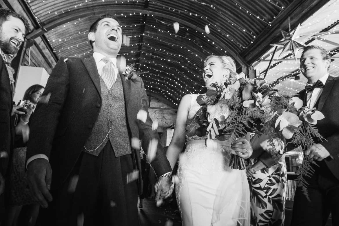 The bride and groom laughing as the guests throw confetti