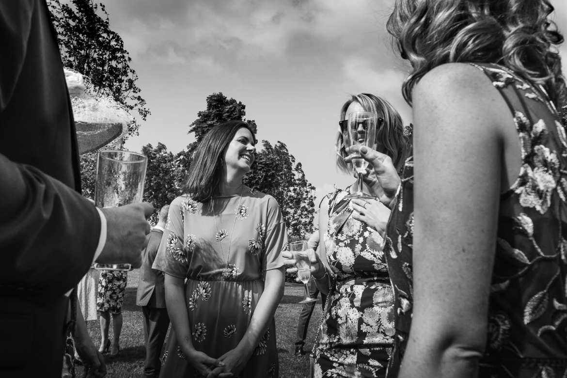 A wedding guests face is distorted by a glass of prosecco