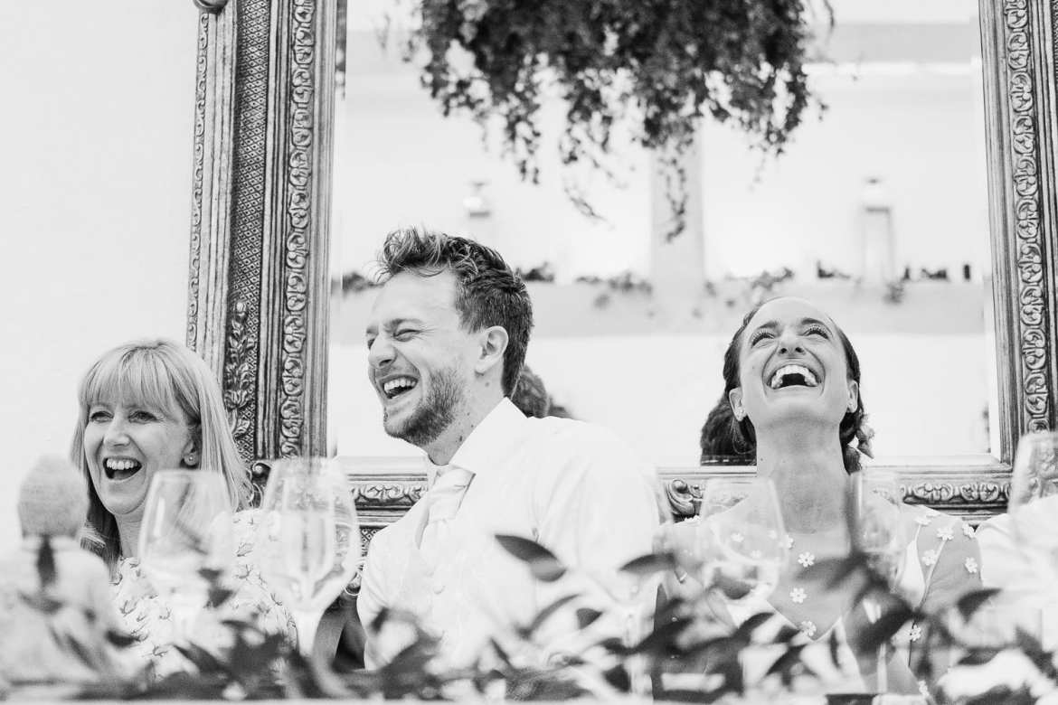 the bride and groom laughing at the best man's speech