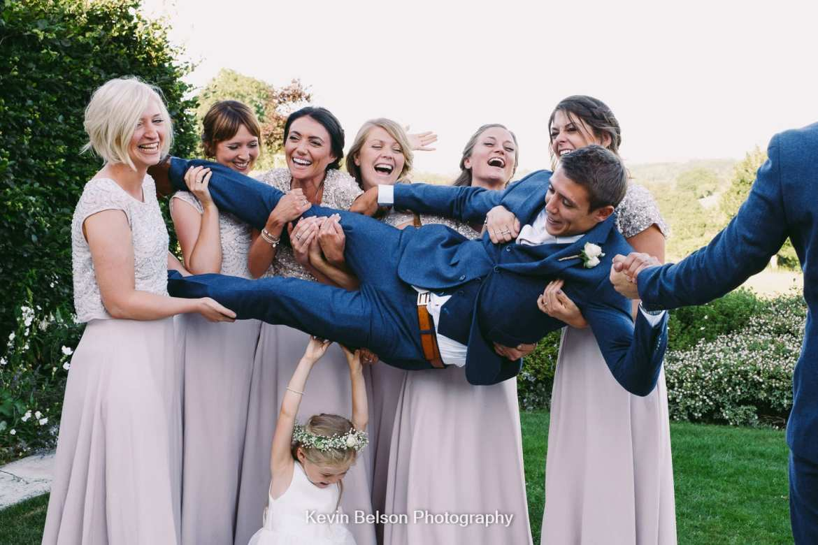 bridesmaids lift the groom