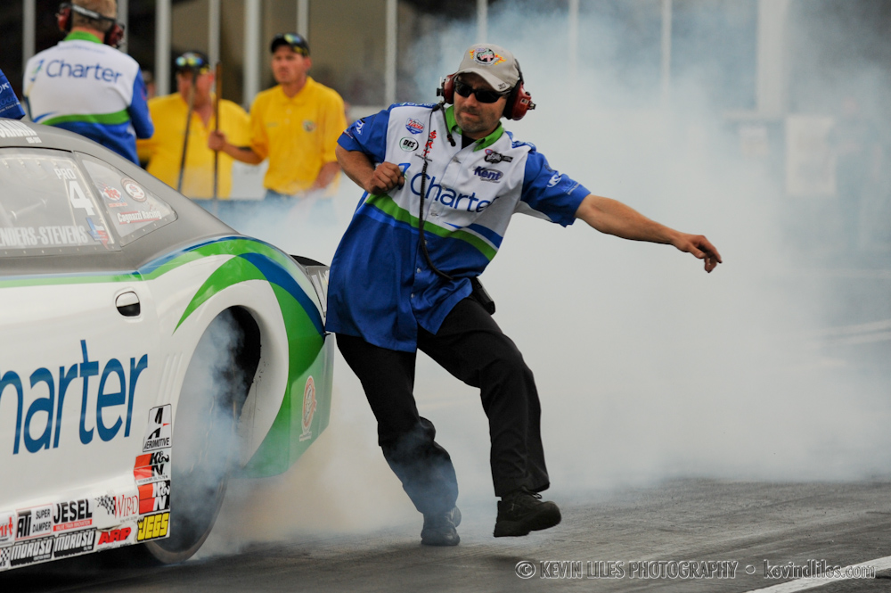 Crew members for pro-stock drivers stand on either side of the car's rear to keep it from sliding side-to-side during burnouts.